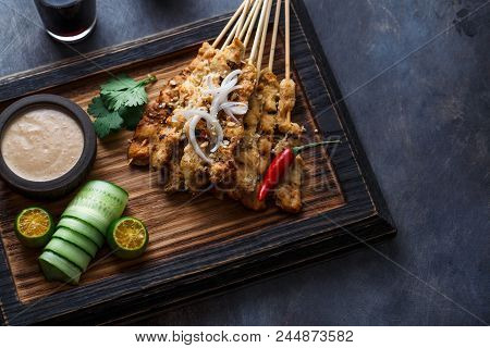 Chicken Satay or Sate Ayam - Malaysian famous food. Is a dish of seasoned, skewered and grilled meat, served with a peanut sauce. Darkphoto. Top view copyspace. stock photo