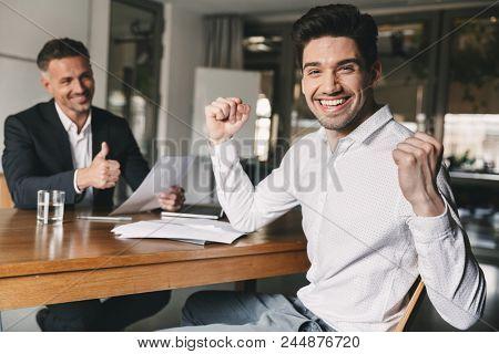 Career, office and placement concept - successful caucasian man 30s rejoicing and clenching fists during job interview with employee of big company stock photo