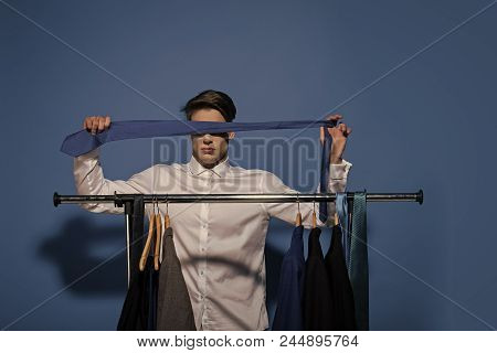 Fashion, accessory, style. Man cover eyes with tie in wardrobe on blue background. Blindfold business concept. stock photo