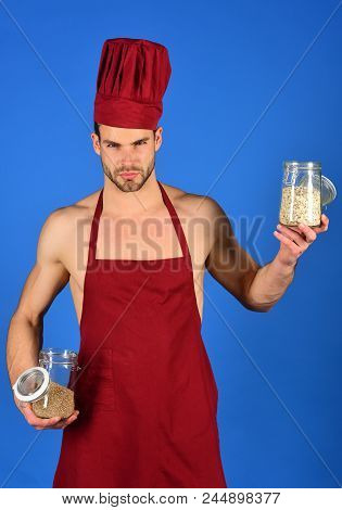 Bearded man in cook uniform. Cooking and professional culinary concept. Food preparation and kitchenware concept. Cook holds jars with cereal. stock photo