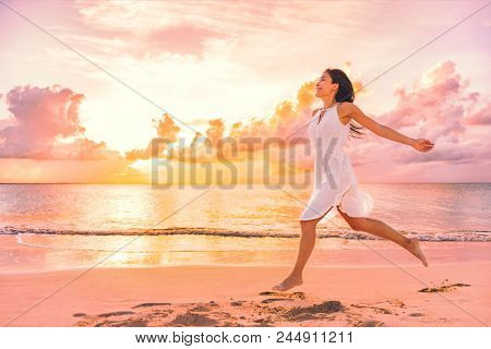 Freedom wellness well-being happiness concept. Happy carefree Asian woman feeling blissful jumping o