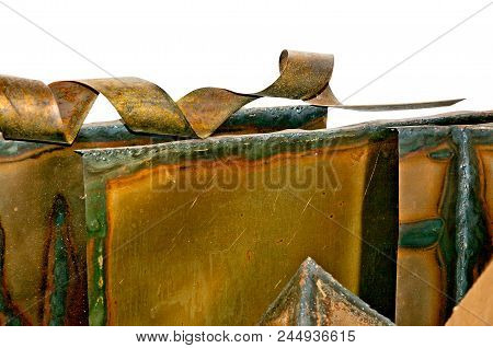 Copper metal sheet oxidized to green on the edge with coiled cut piece isolated on white. stock photo