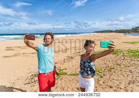 Self absorbed young people taking selfie pictures of themselves on beach vacation. Social media addiction, two friends holding smart phones, funny concept. stock photo