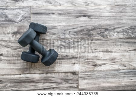 Training at home fitness concept: dumbbell weights on wood floor at fitness gym . Weight loss and he