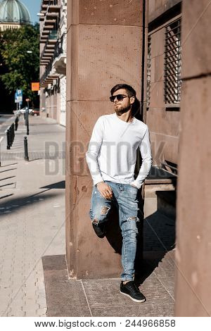 Young man on the street. Stylish guy in the glasses near the building. A cute man waits for a meeting. Men's Thoughts. Man sitting on the sidewalk. Warsaw, Poland, Polska, Warszawa. student after classes, school, student, classes, education, happy, colleg stock photo