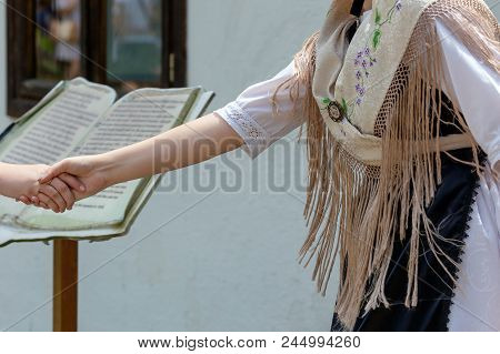 Friendly and significant hand-to-hand between a German ethnic group and other ethnicities in Banat, Romania. Banat area is recognized as a model of peaceful coexistence between several ethnic groups stock photo