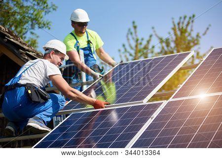 Two professional technicians installing heavy solar photo voltaic panels to high steel platform. Exterior solar system installation, alternative renewable green energy generation concept. stock photo