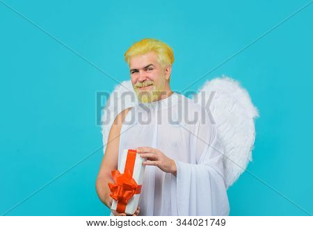 February 14. Cupid with gift. Love concept. Cupid with gift box. Valentine angel. Cupid angel with present box. Happy Valentines Day. Smiling man in angel costume. Valentines day angel. Cupid. Amour stock photo