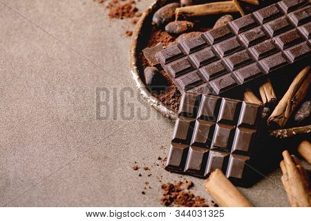 Dark and milk chocolate bar whole and chopped with cocoa beans, cocoa powder and cinnamon sticks over brown texture background. Close up, copy space stock photo