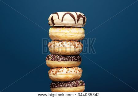 Stack of assorted delicious colorful donuts near dark blue background, sugar concept close-up stock photo