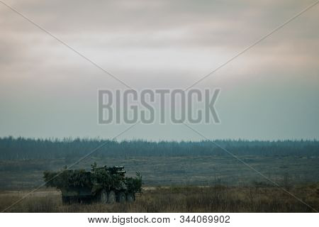 Military patrol car on a field. Army war concept. Armored vehicle with gun in action. Decorated. stock photo