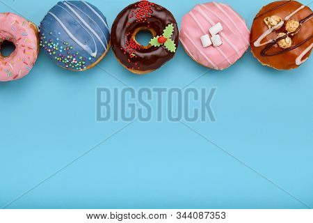Top view of assorted donuts on blue background with copy space. Colorful donuts background. Various glazed doughnuts with sprinkles. stock photo