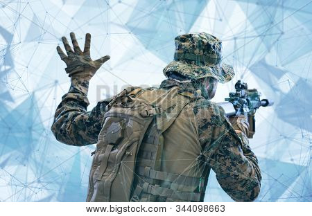 modern warfare soldier in action giving comands to team by hand signs while sneaking and aiming  on laseer sight optics  in combat position and  searching for target in battle stock photo