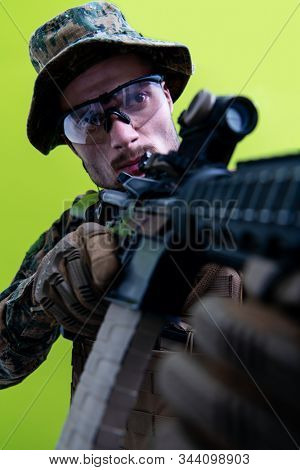 modern warfare american marines soldier in action while sneaking and aiming  sniper riffle on laseer sight optics  in combat position and  searching for target in battle green background stock photo