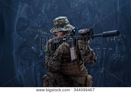 modern warfare american marines soldier in action while sneaking and aiming  sniper riffle on laseer sight optics  in combat position and  searching for target in battle stock photo