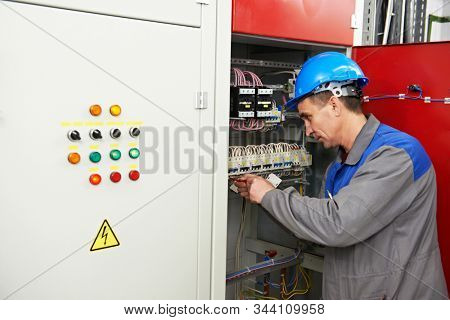 electricianat work in electric distribution switching cabinet stock photo