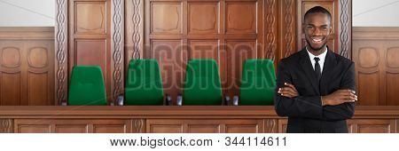 Confident Attorney In Courtroom Standing Arms Crossed stock photo