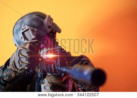 modern warfare american marines soldier in action while sneaking aiming  on laseer sight optics  in combat position and  searching for target in battle yellow background stock photo