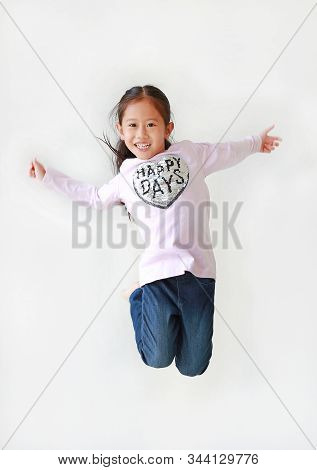Smiling little Asian child girl freedom movement jumping in air over white background. stock photo