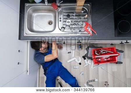 High Angle View Of Male Plumber In Overall Fixing Sink Pipe stock photo