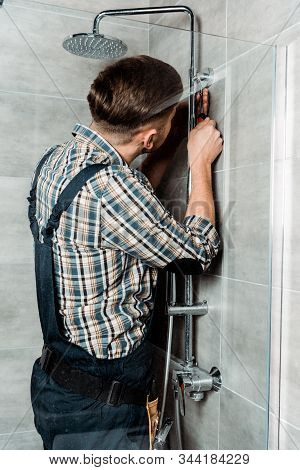 installer standing in bathroom and installing pipe near shower head stock photo