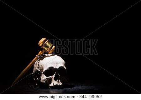 Legal law, justice and murderment concept. Wooden judge gavel hammer on human skull with handcuffs against black background. Free space. stock photo