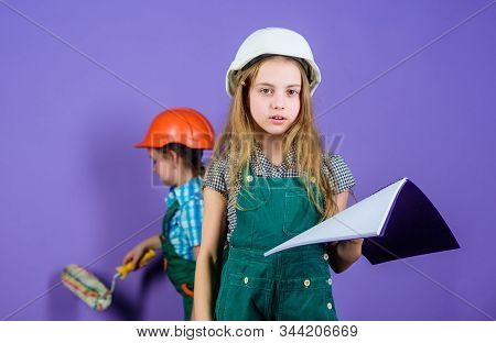 Kids girls planning renovation. Repaint walls. Move in new apartment. Children sisters run renovation their room. Control renovation process. Sisters happy renovating home. Home improvement activity stock photo