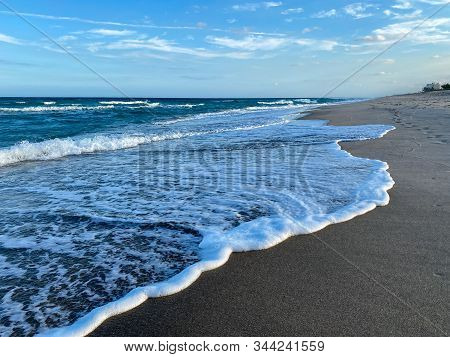 Ocean waves lapping on the beach  on a beautiful sunny day along the shoreline on North Hutchinson Island Florida. stock photo