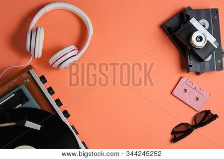 Flat lay retro 80s pop culture objects. Vinyl player, headphones, audio cassette, video tapes, film camera on coral color background. Copy space. Top view stock photo