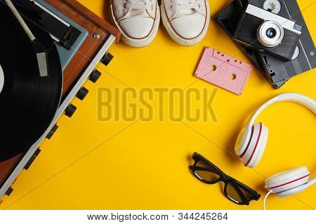 Flat lay retro 80s pop culture objects. Vinyl player, headphones, audio cassette, video tapes, film camera, sneakers on yellow background. Copy space. Top view stock photo