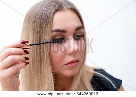 Beautiful girl applying mascara. Portrait of a beautiful girl applying mascara stock photo
