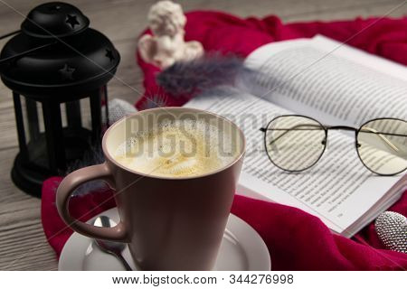 A mug of latte next to an open book on which there are glasses on the worm of a beautiful red background candlestick and angel stock photo