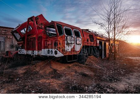 Old rusty broken abandoned Soviet fire truck on evening sunset stock photo