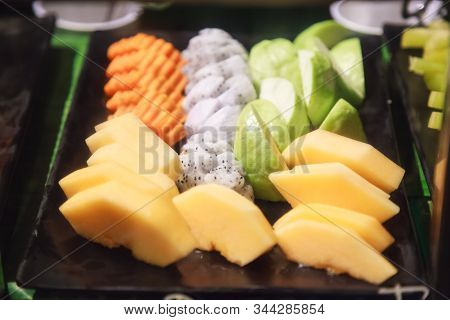 Fresh assorted tropical Asian seasonal fruits serving (guava, dragon fruit, papaya, cantaloupe) in black tray. Vegetarian and Vegan Food, Natural and Organic Fruit, Nutrition and Health care concept. stock photo