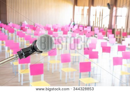 Close up microphone on stage and chairs are background in the large meeting room. stock photo