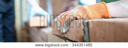 Close-up of careful man laying red bricks on well made masonry. Craftsman wearing special gloves to protect arms. Smart constructor using special tools and equipment. Building concept stock photo