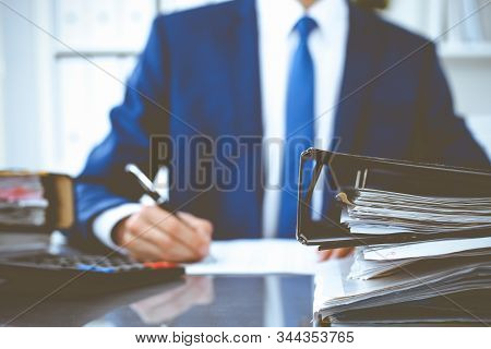 Binders with papers waiting to be processed with businessman or bookkeeper back in blur. Accounting planning budget. Audit, insurance and business concept stock photo