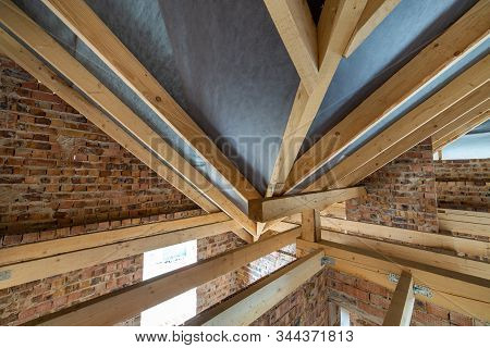 Attic space of a building under construction with wooden beams of a roof structure and brick walls. Real estate development concept. stock photo