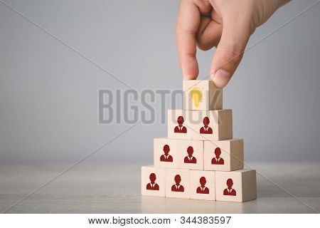 Hand choosing wood cube with icon light bulb and human symbol,creative idea and innovation concept. stock photo