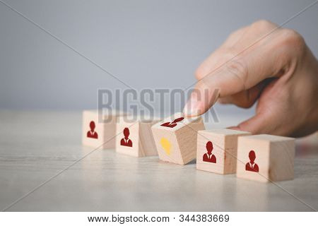 Hand arranging flips wood block with icon light bulb and human symbol, stock photo