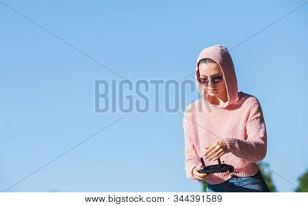 Young woman wearing sunglasses and hoodie holding a remote control, controls, controls are not visible in the frame drone. A woman carefully looks into the distance against a blue sky. Copyspace. stock photo