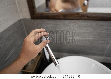 Male hand use a faucet in a bathroom interior with white round sink and chrome faucet. Water flowing from the chrome faucet. stock photo