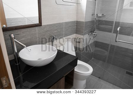 Bathroom interior with white round sink and chrome faucet in a modern bathroom with a toilet and shower. Water flowing from the chrome faucet. stock photo