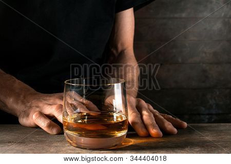 Man's hand reaches for a glass of alcohol. Conceptual image on the subject of alcoholism. Copy space for your text. stock photo