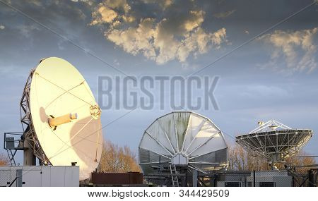 Satellite dish large and antenna for communication and mobile technology network during sunset group with bright light stock photo