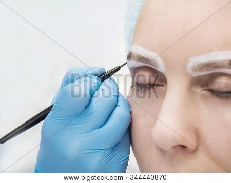 Eyebrow shadow applying, brow modelling makeup, eye closeup. Beautician Doing Eyebrow Tattooing For Female Face. Beauty Procedure stock photo