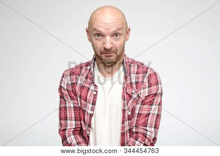 Bald man is frightened, his secret is revealed, he looks into the camera with big eyes and does not know how to proceed. Isolated on white background. stock photo