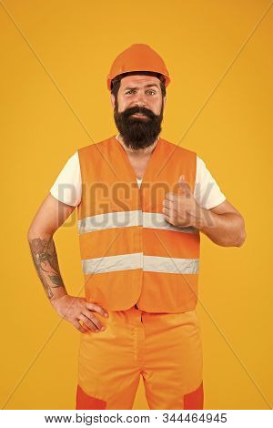 Confident in building. Confident constructor. Bearded man worker showing thumbs up with confident look. Happy builder or architect with confident smile on yellow background. stock photo