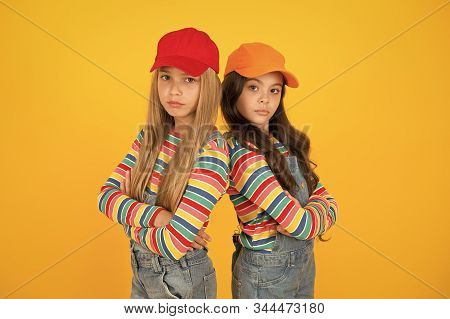Fashion that matches their conscious style. Small girls in style keeping arms crossed on yellow background. Little children wearing baseball caps in casual streetwear style. Hip hop or hipster style. stock photo