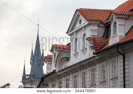 Austro-Hungarian Facade of a baroque appartment residential building in a street of old town, the historical center of Prague, Czechia in the most touristic part of the city, with an iconic tower in background. stock photo